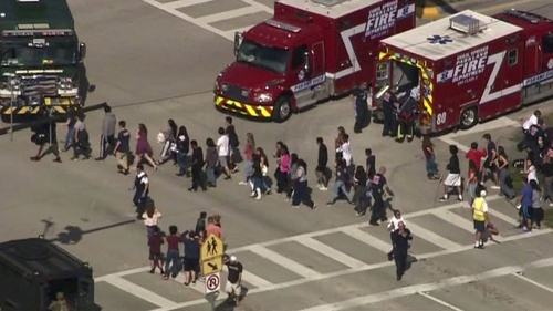 Students are evacuated from Marjory Stoneman Douglas High School during a shooting incident in Parkland