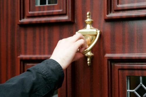 mans hand using door knocker on wood effect upvc door cold calling household